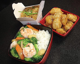 Assorted Chinese food entrees including shrimp and broccoli, honey sesame chicken and pork and egg fried rice